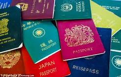 image of a pile of passports in various colours from around the world